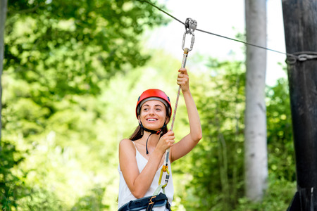 jungle girl: Young and pretty woman in red helmet riding on a zip line in the forest. Active sports kind of recreation