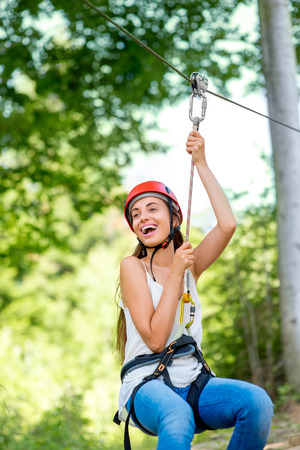 Young and pretty woman in red helmet riding on a zip line in the forest. Active sports kind of recreation Stok Fotoğraf - 43573674