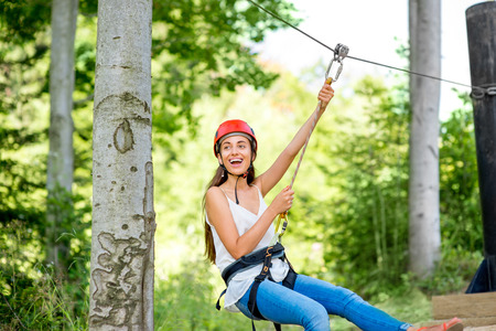 Young and pretty woman in red helmet riding on a zip line in the forest. Active sports kind of recreation