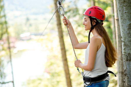 casco rojo: Mujer joven y sonriente en casco rojo se prepara para montar en una tirolesa en el bosque. Cierre de vista centrado en manos y cara Foto de archivo
