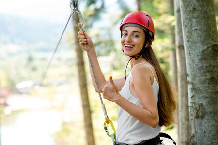 casco rojo: Young and smiling woman in red helmet preparing to ride on a zip line in the forest. Close up view focused on hands and face