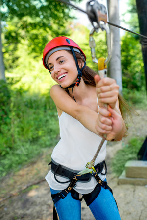 casco rojo: Young and pretty woman in red helmet enjoying riding a zip line in the forest. Active summer sports recareation