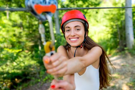 casco rojo: Mujer joven y bonita en casco rojo disfrutando de montar una tirolesa en el bosque. Activo recareation Deportes de verano