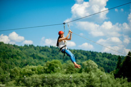 Young woman in casual wearing with red helmet riding on a zip line in the mountains. Active kind of recreation