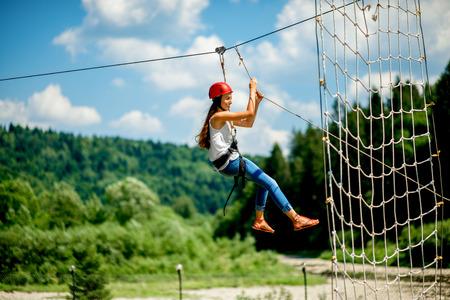 カジュアルな山でジップ ・ ラインに乗って赤いヘルメットを身に着けている若い女性。レクリエーションの活動の種類