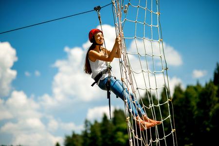 casco rojo: Mujer joven en el usar ocasional con paseos casco rojo en una tirolesa en las montañas. Especie activa de recreación
