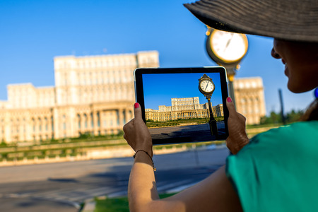 old buildings: Female hands photographing with digital tablet parliament building in Bucharest, Romania Stock Photo