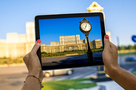 rumania: Female hands photographing with digital tablet parliament building in Bucharest, Romania Stock Photo