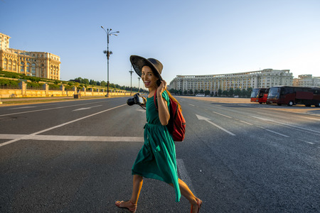rumania: Young woman traveler running with backpack and photo camera in the center of Bucharest city Stock Photo