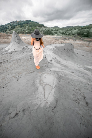 subduction: Young female traveler with photocamera walking near mud volcanoes in Buzau in Romania