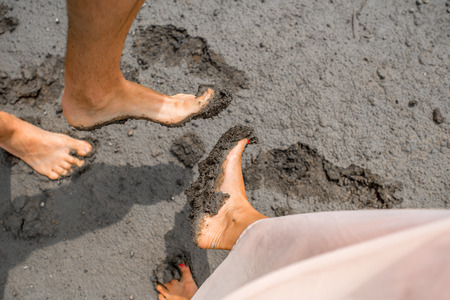 Couple showing feet smeared in the mud