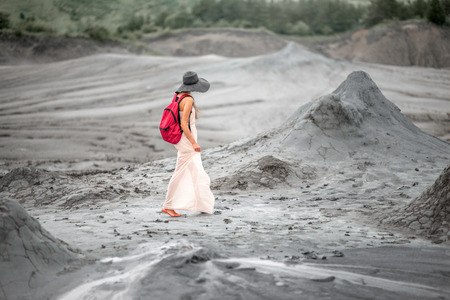 subduction: Young female traveler in hat and red backpack walking near mud volcanoes in Buzau in Romania
