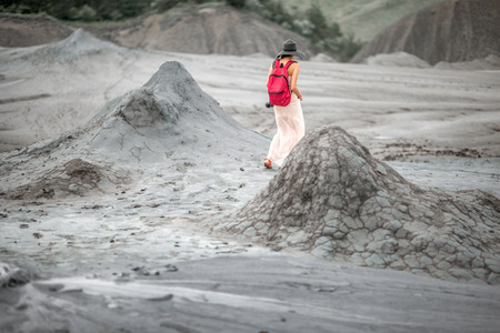 Young female traveler in hat and red backpack walking near mud volcanoes in Buzau in Romania