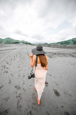 Young female traveler with photocamera walking near mud volcanoes in Buzau in Romania