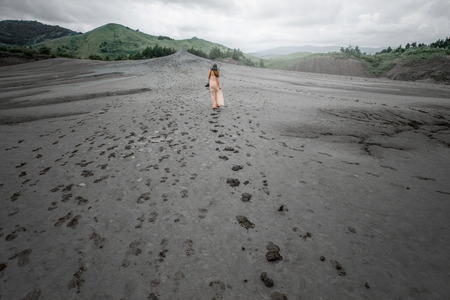 Young female traveler walking near mud volcanoes in Buzau in romania Stock Photo