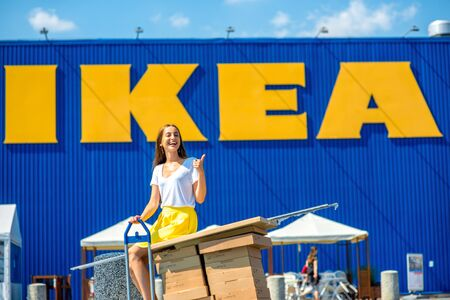 IKEA の店の前に立ってボックスとワルシャワ, ポーランド - 2015 年 8 月 5 日: 若くて幸せな女性。IKEA は、世界最大の家具の小売商であります。