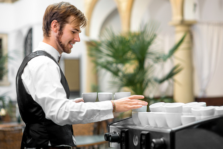 waiter serving: Young waiter serving coffee cups on the coffee machine Stock Photo