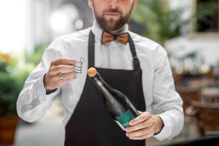 Knappe barman in uniform opening fles met mousserende wijn buiten op het terras van het restaurant