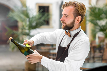 butterfly knife: Handsome barman in uniform opening bottle with sparkling wine outdoor on the restaurant terrace. Sabrage - method of opening sparkling wine Stock Photo