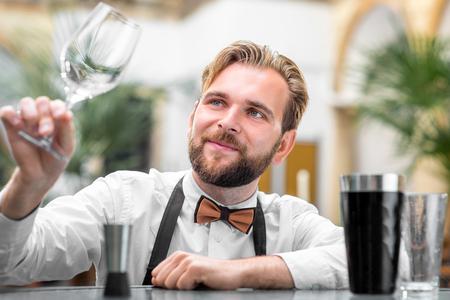 limpieza: Camarero elegante comprobar la limpieza de vidrio en el restaurante Foto de archivo