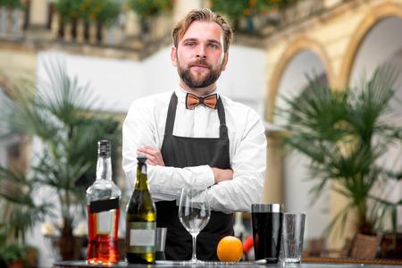 Portret van knappe barman in uniform met flessen en shaker in het restaurant Stockfoto
