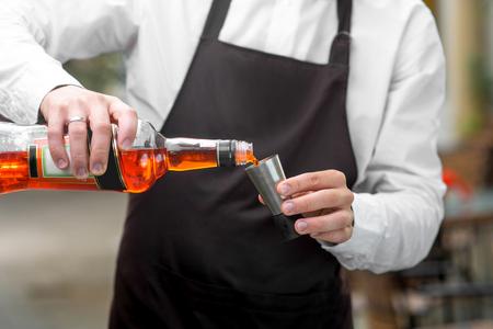 mandil: Barman en el delantal oscuro vertiendo Aperol al dosificador de metal