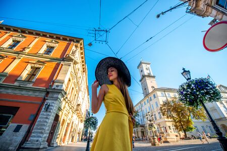 Beautiful female traveler with hat and yellow dress walking in the center of old city in Lviv