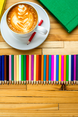 ?text space?: Group of colorful pencils with coffee cup and books on the wooden table. Top view with text space