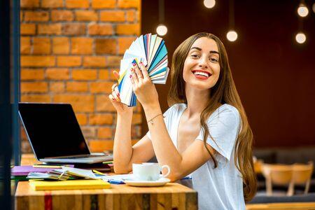 color in: Dise�ador joven en papel de la elecci�n de la ropa informal de muestras de color sentado en el caf� con el ordenador port�til y una taza de caf�