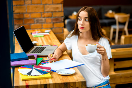 interior office: Young woman drawing with colorful pencils and holding a cup of coffee sitting in the cafe