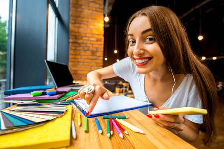 persistent: Playful and persistent girl studing with colorful stuff in the modern cafe interior