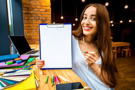 working space: Young and smiling woman showing board with white paper on the colorful working space background