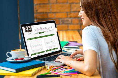 ESTADISTICAS: Mujer joven que trabaja con las estadísticas en la computadora portátil con lápices de colores, libros y una taza de café sobre la mesa en el backround pared de ladrillo en la cafetería o en la oficina