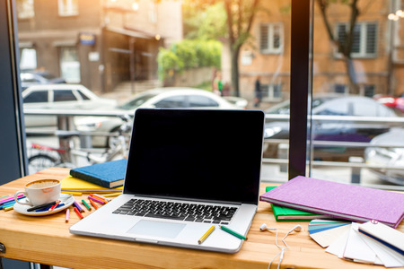 Working place with laptop, colorful pencils, books, earphones and a cup of cooffee on the wooden table near the window Stock Photo
