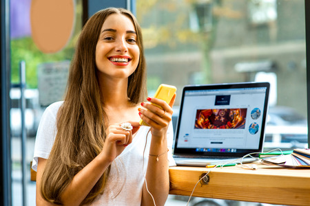 Young woman using yellow smart phone sitting near the window with laptop and colorful stuff on the table in the cafe Banco de Imagens