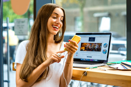 Young woman using yellow smart phone sitting near the window with laptop and colorful stuff on the table in the cafe Stock Photo
