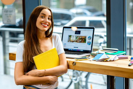 Young female student holding yellow book with laptop and colorful stuff on the table near the window with street view in the cafe or studio