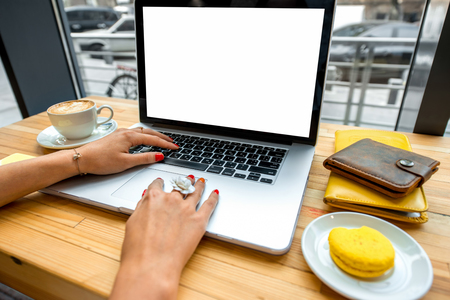 yellow notepad: Female hands typing on the laptop with coffee cup, phone, sweet cake and wallet on the wooden table