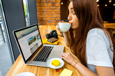 Young woman enjoying cappuccino sitting with laptop in the wooden cafe interior. Coffee break concept Archivio Fotografico
