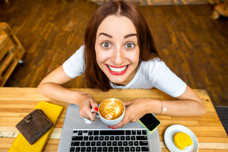 Young woman enjoying cappuccino sitting with laptop in the wooden cafe interior. Top view Foto de archivo