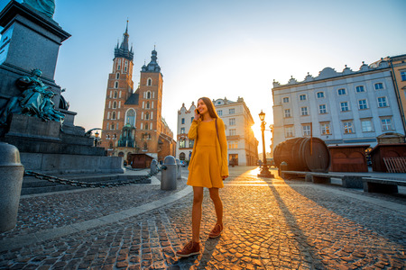 mickiewicz: Young and beautiful woman in yellow dress walking and talking with mobile phone in the old city center of Krakow on the morning sunrise