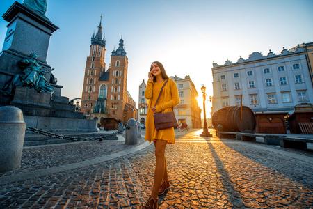 personas platicando: Mujer joven y hermosa en vestido amarillo caminando y hablando con el tel�fono m�vil en el casco antiguo de la ciudad de Cracovia en el amanecer de ma�ana
