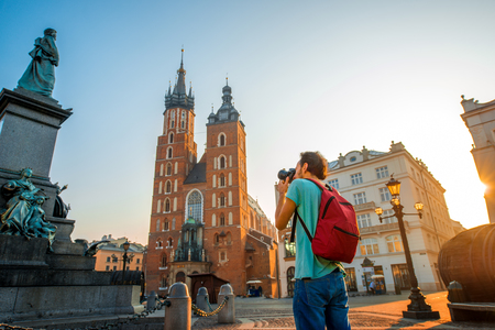 city of sunrise: Male tourist with backpack photographing famous Polish basilica in the center of Krakow Stock Photo