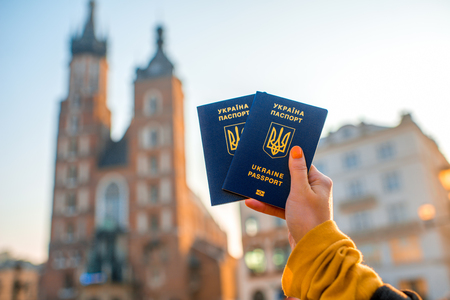 cracow: Female hands holding Ukrainian abroad passports on the Krakow city center background. Traveling to Europe from Post-Soviet countries or emigration to Europe concept Stock Photo