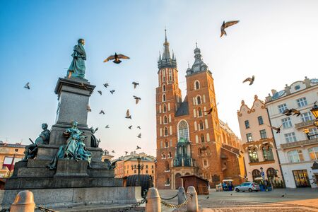 mary's: Old city center view with Adam Mickiewicz monument, St. Marys Basilica and birds flying in Krakow on the morning Stock Photo