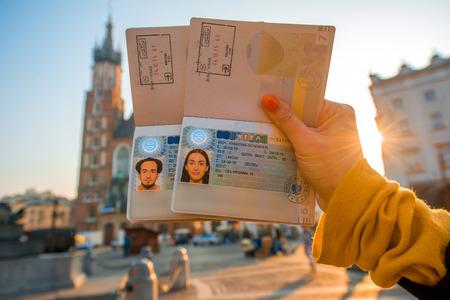 クラクフ シティ センターの背景に Shengen ビザとウクライナのパスポートを保持している女性の手。ソ連崩壊後の国の概念からヨーロッパへの旅 写真素材