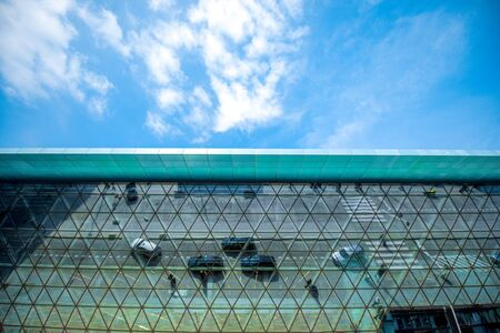 crowded space: Modern airport terminal facade with cars and peoples reflections. Wide angle view with copy space