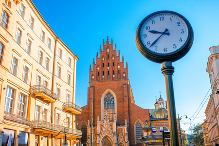 holy: View on Holy Trinity church with city clock in Krakow town
