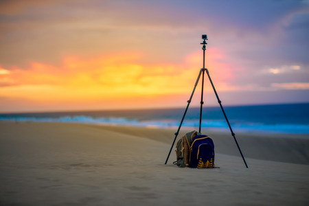 nature photo: Small video camera on the tripod with backpack on the sand dunes on the beautiful sky background. Stock Photo