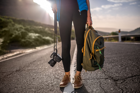 without legs: Female traveler holding photocamera and backpack standing on the mountain road. Medium plan view without face focused on legs